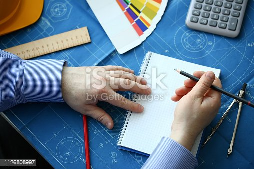 istock Hands of an engineer in shirt at workplace 1126808997