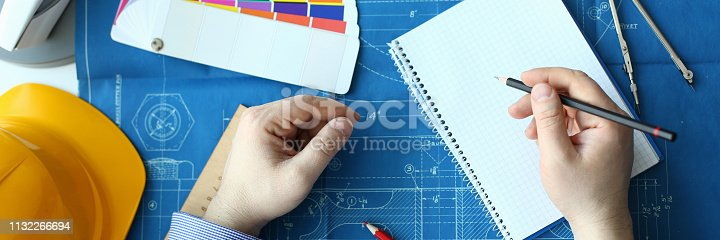 istock Hands of an engineer in shirt at workplace 1132266694