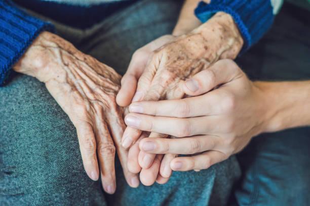 hände eine alte frau und ein junger mann. pflege für ältere menschen. nahaufnahme - hospiz stock-fotos und bilder