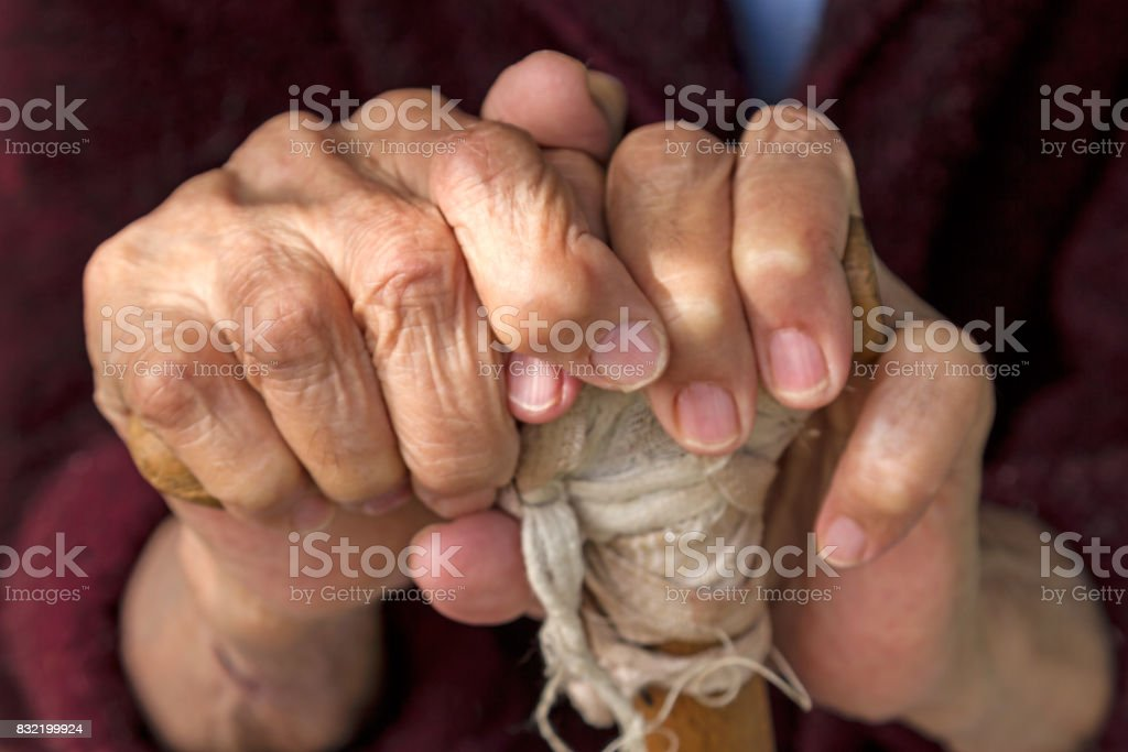 Hands of an old woman on a wooden crutch stock photo