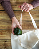 Hands of an old woman put fresh organic avocado in Eco Shopping Bag on wooden background, Flat Lay