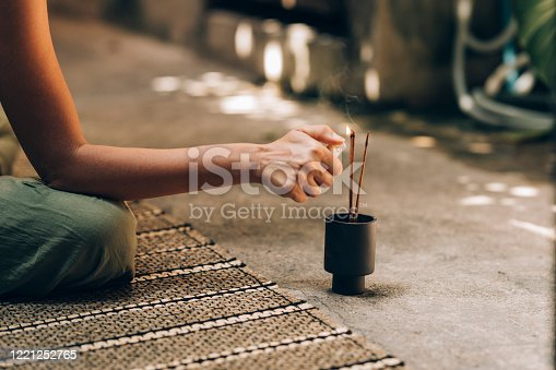 Happy woman lighting incense sticks to support her yoga practice.