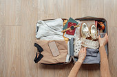 From above photo of hands of unrecognisable woman packing her suitcase.