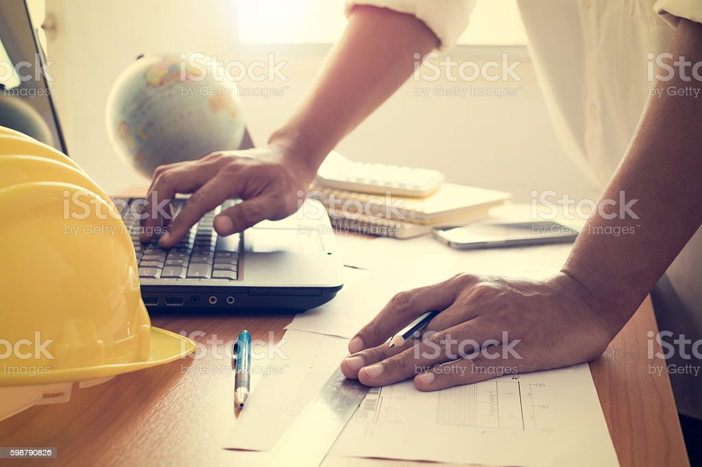 Hands of architect working on laptop with construction plan stock photo