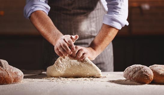 istock hands of baker's male knead dough 1025971168
