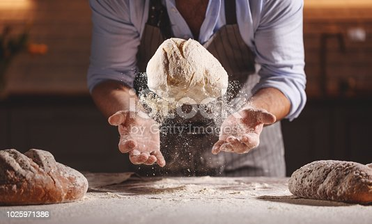 hands of the baker's male knead dough
