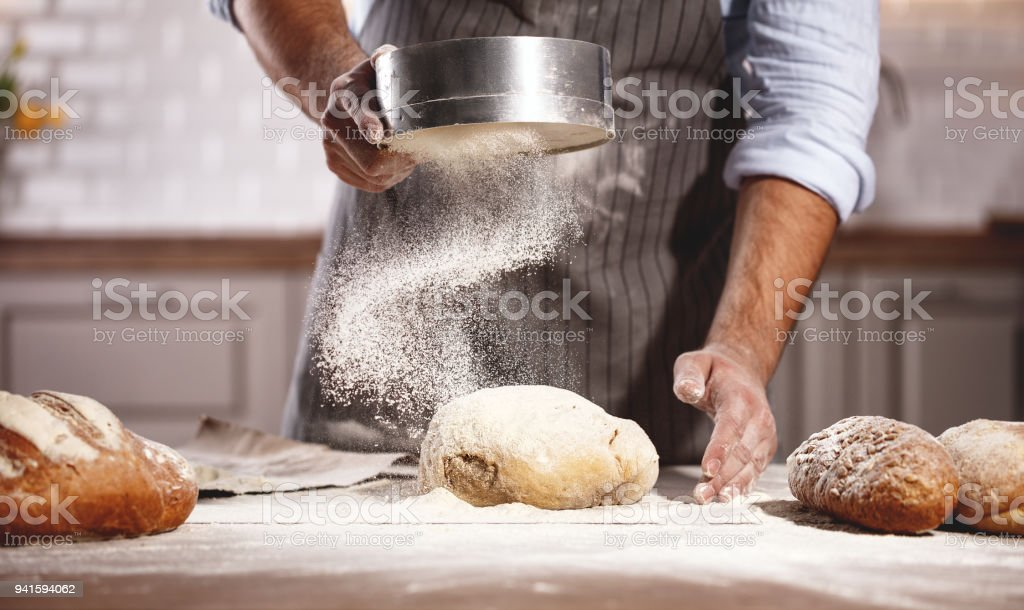 hands of baker's male knead dough stock photo