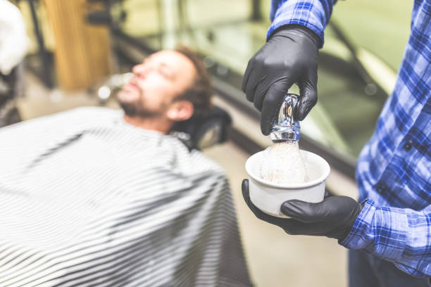 Hands of barber with brush for shaving beard and bowl. barber shop Close up of barber hands preparing foam by using shaving brush and bowl. Client in armchair in the background. shaving brush shaving cream razor old fashioned stock pictures, royalty-free photos & images