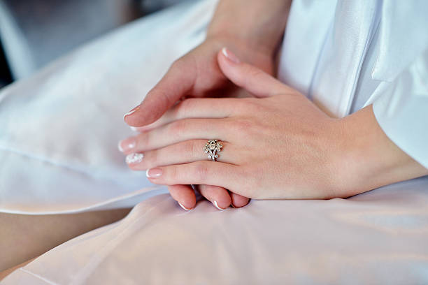 Hands of beautiful bride in white dressing gown stock photo