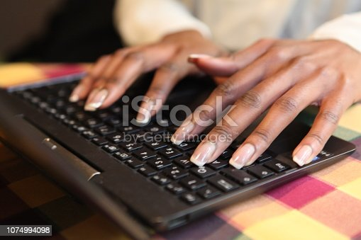 939030682 istock photo Hands of black girl typing on her laptop at a desk 1074994098