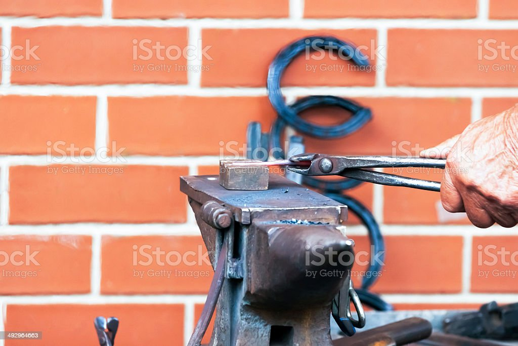 Hands of Blacksmith-Farrier shaping horseshoe, copy space royalty-free stock photo
