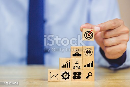 hands of busines hold a target with arrow,stacking wooden blocks into steps,Concept of business growth success