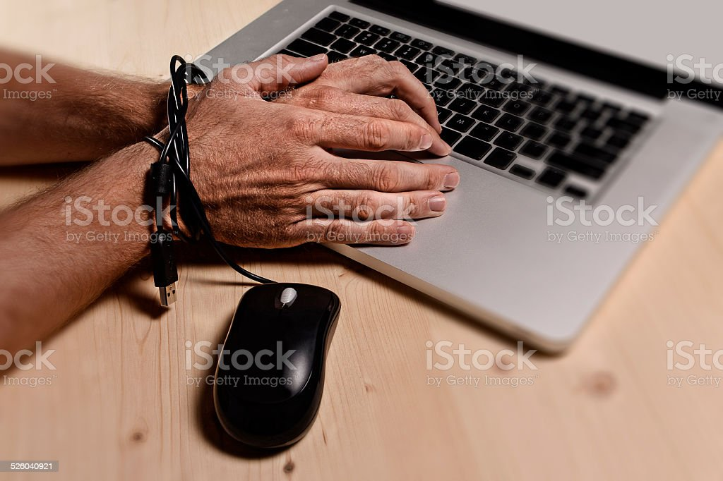 Hands of businessman addicted to work bond with mouse cable stock photo