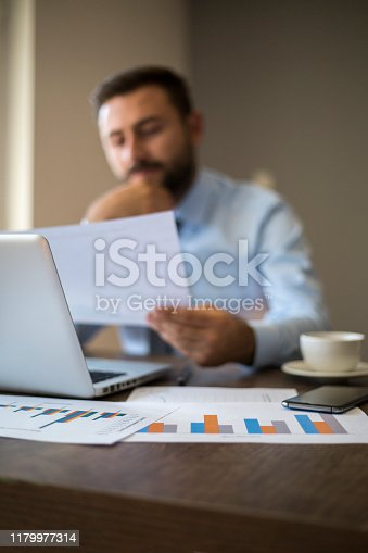 801895196istockphoto Hands of Businessman Notebook and documents working 1179977314