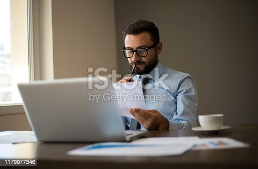 801895196istockphoto Hands of Businessman Notebook and documents working 1179977346