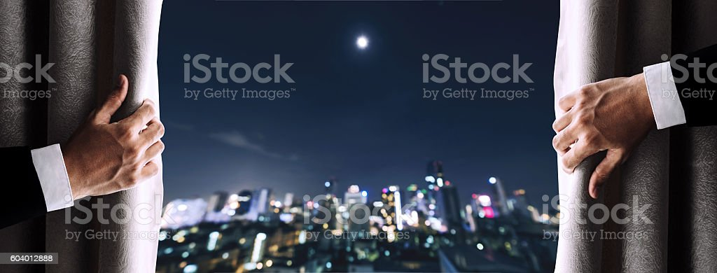 Hands of businessman opening curtain with Bokeh of Bangkok city stock photo