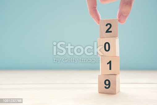 istock Hands of businessman putting wood cube text new year 2019 1031232766