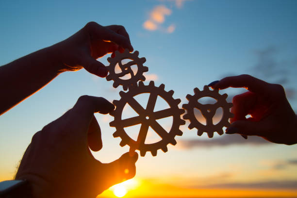 hands of businessmen assemble a puzzle from gears against the sky in the sunset. stock photo