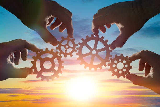 hands of businessmen assemble a puzzle from gears against the sky in the sunset stock photo