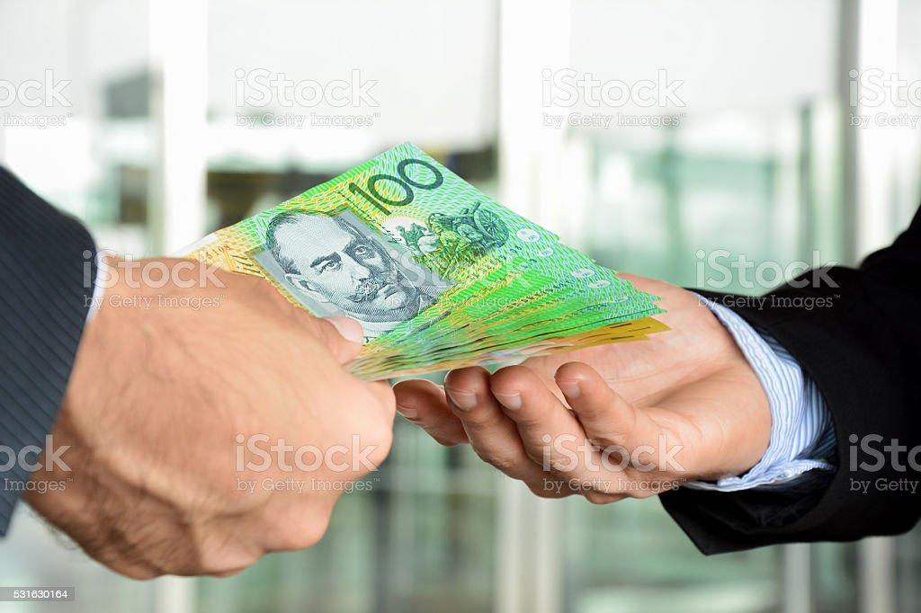 Hands of businessmen passing money, Australia dollar bills stock photo