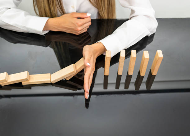 Hands of businesswoman stop block a wood game, gambling placing a wooden block. Concept Risk of management and strategy plan, protect business to success. stock photo