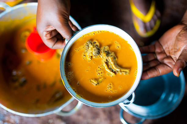 hands of cameroonian woman holding pot of traditional taro with sauce jaune dish in african kitchen stock photo