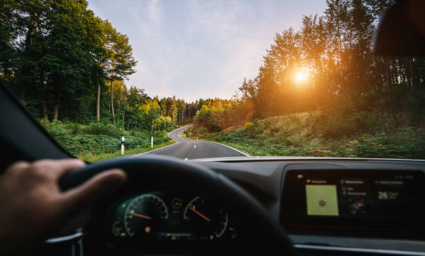 hands of car driver on steering wheel, road trip, driving on highway road stock photo