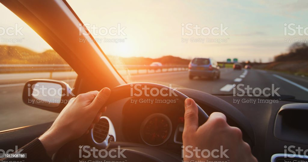 hands of car driver on steering wheel, road trip stock photo