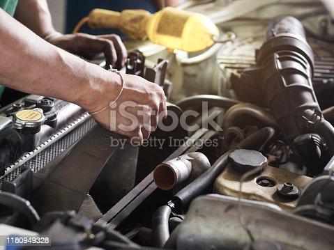 Hands of car mechanic holding the fan of Radiator in garage. Car repair