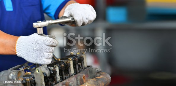 1073743202 istock photo Hands of car mechanic in auto repair service in automobile garage 1199571966