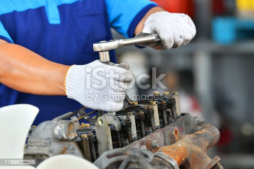 1073743202 istock photo Hands of car mechanic in auto repair service in automobile garage 1199572055