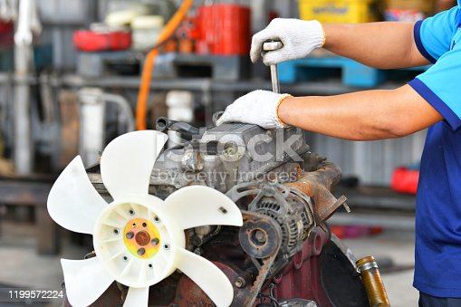 1073743202 istock photo Hands of car mechanic in auto repair service in automobile garage 1199572224
