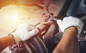 istock Hands of car mechanic in auto repair service. 1023361004