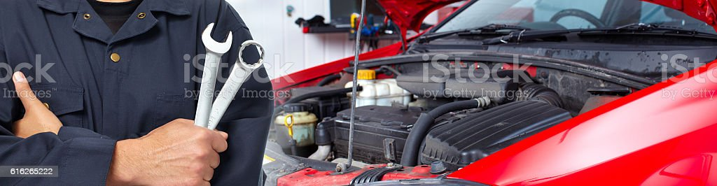 Hands of car mechanic with wrench in garage. stock photo