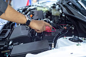 Hands of car mechanic working in battery check.