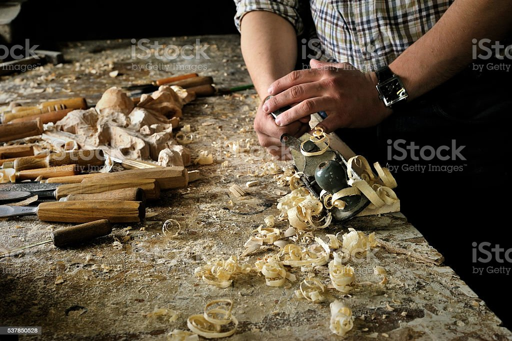Hands of carver work with jointer in workshop stock photo