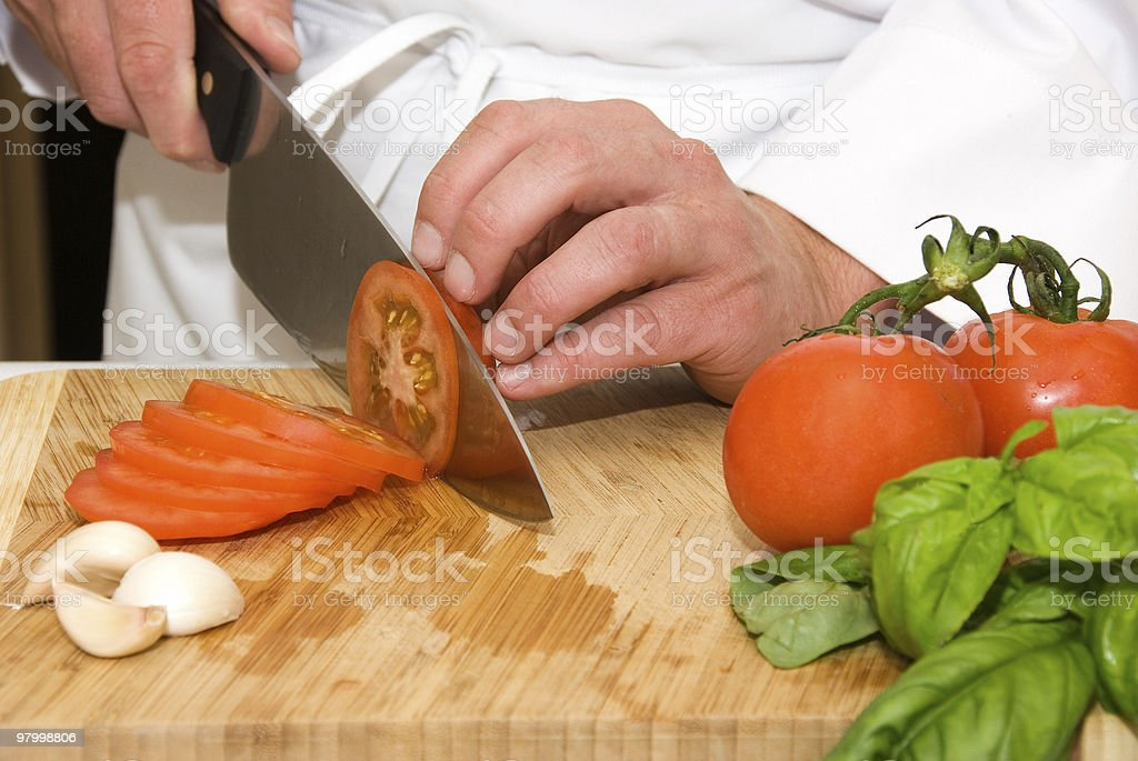 Hands of chef cutting a tomato royalty free stockfoto