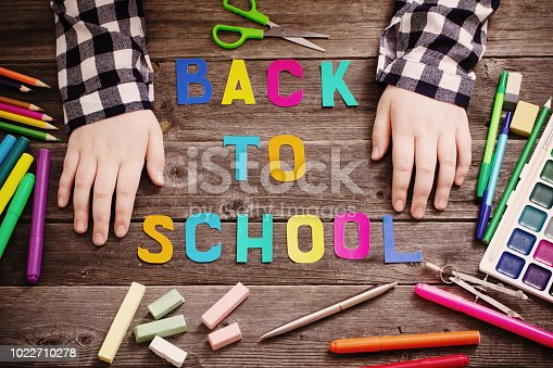 istock hands of child on  table with school supplies 1022710278