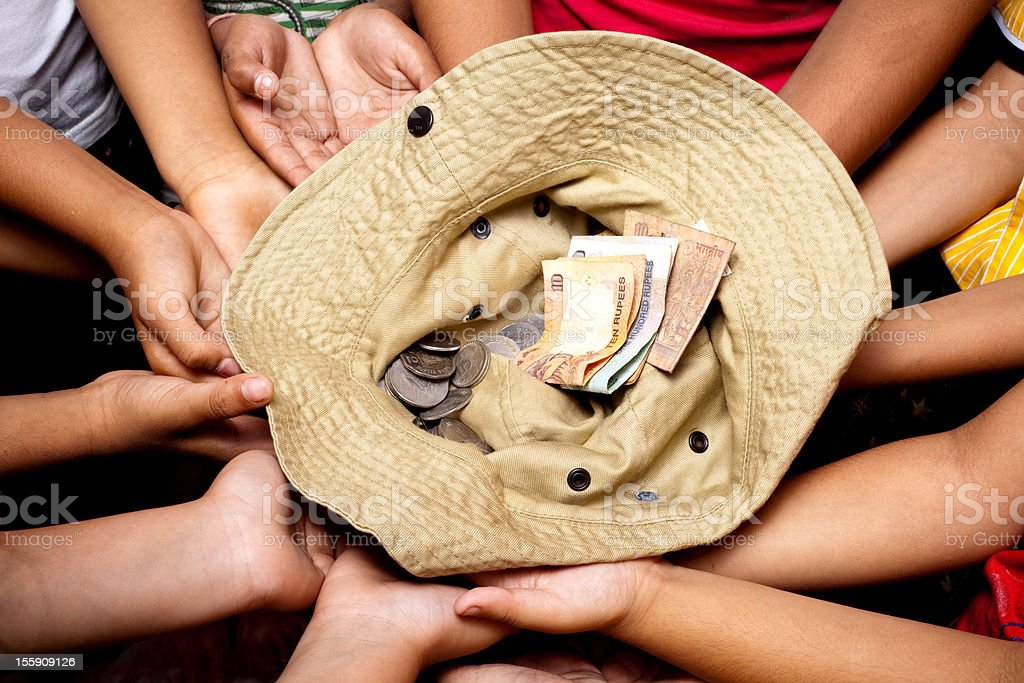 Hands of Children collecting money donation for Charity in Hat royalty-free stock photo