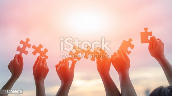 istock Hands of children students holding pieaces of jiwsaw together as a symbol for autism or teamwork in school. 1132265679