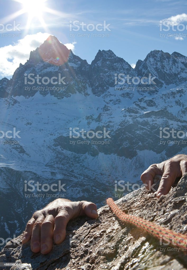 Hands of climber grasp rock ledge, mountains behind stock photo