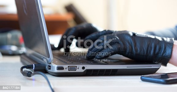 istock Hands of Computer Hacker in black Gloves working on Laptop 840177184