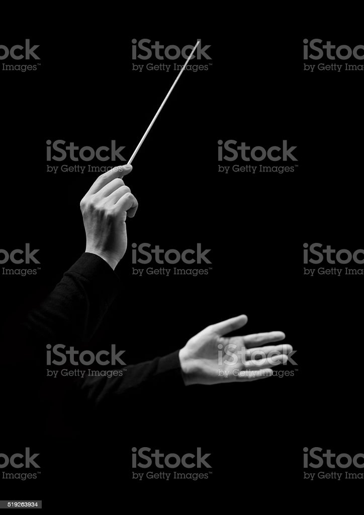 Hands of conductor on a black background stock photo