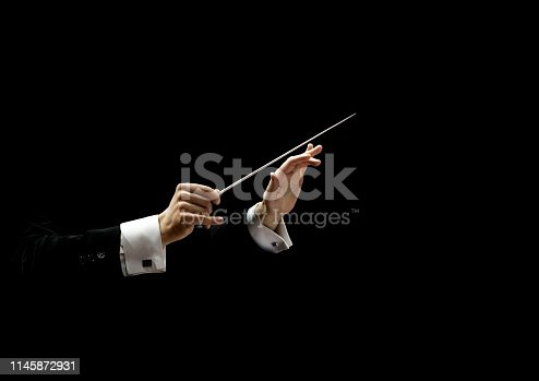 Hands of conductor on a black background