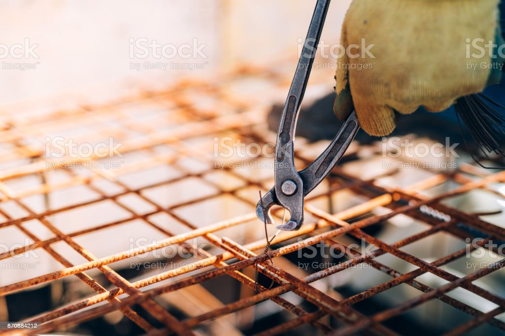hands of construction worker using pliers and securing steel bars with wire rod for reinforcement of concrete or cement stock photo