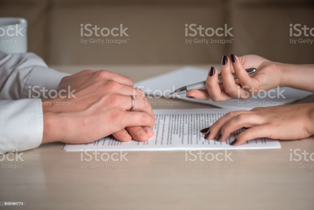 Hands of contractual parties, a woman and a man, signing a contract stock photo