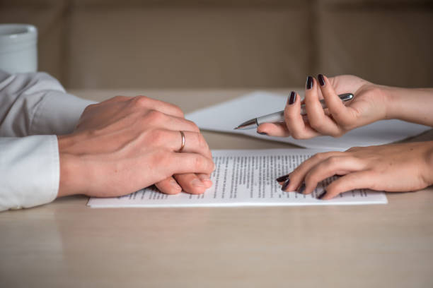 hands of contractual parties, a woman and a man, signing a contract - divorzio foto e immagini stock