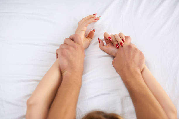 Hands of couple in bed. stock photo