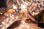istock Hands of couple with flutes of champagne and their friends with bengal lights 1195253750