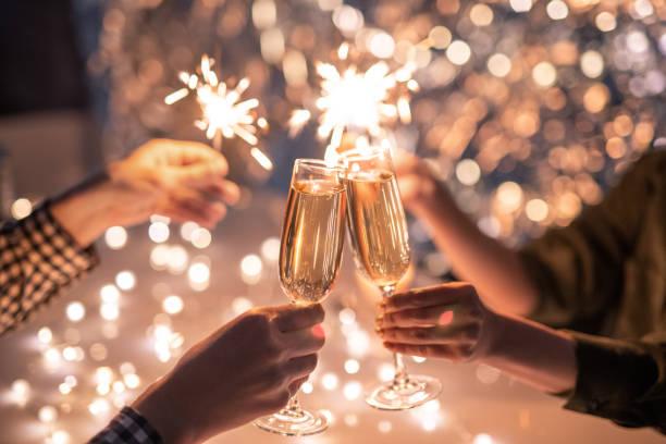 manos de pareja con flautas de champán y sus amigos con luces de bengala - año nuevo fotografías e imágenes de stock
